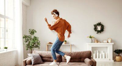 Plakat Cheerful woman listening to music and dancing on soft couch at home in day off.