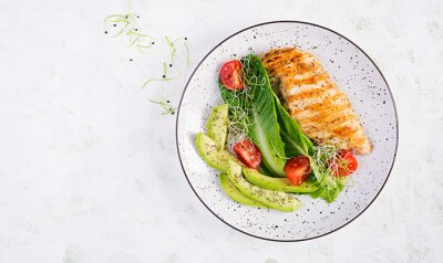 Chicken grilled fillet with salad fresh tomatoes and avocado. Healthy food, ketogenic diet, diet lunch concept. Keto/Paleo diet menu. Top view, flat lay