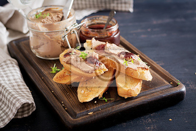 Chicken homemade liver paste or pate in glass jar with toasts and lingonberry jam with chili. Copy space