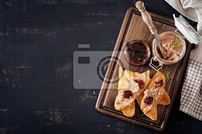 Chicken homemade liver paste or pate in glass jar with toasts and lingonberry jam with chili. Top view, copy space