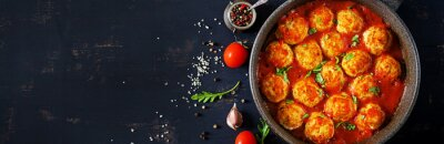 Chicken meatballs with tomato sauce in a pan. Dinner. Top view. Banner.  Dark background.