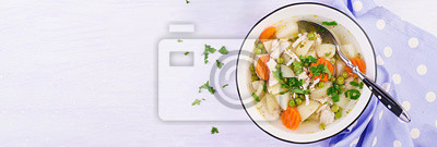 Chicken soup with green peas, carrots and potatoes in a white bowl on a light background. Banner. Top view