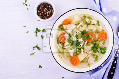 Chicken soup with green peas, carrots and potatoes in a white bowl on a light background. Top view
