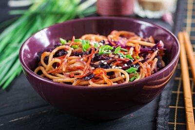 Chińskie jedzenie. Wegańskie mieszać smażyć makaron z czerwoną kapustą i marchewką w misce na czarnym drewnianym tle. Dania kuchni azjatyckiej.