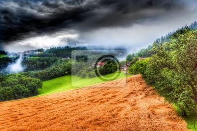 Ciężka pogoda na letni wieczór nad krajobrazem wiejskim z polami, drzewa, farmy, lasu, łąki, chmur i mgły w kolorze stylu malarstwa vintage