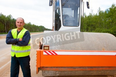 Ciężki rolki drgań i pracownik przemysłowy podczas budowy dróg