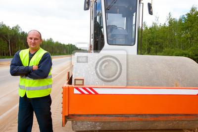Ciężki walec wibracyjny i pracowników podczas budowy drogi