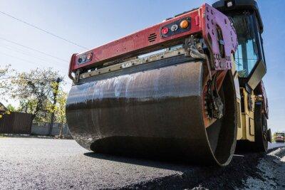 Ciężki wałek wibracyjny na nawierzchni asfaltowej działającej na nowej budowie drogi. Naprawa.