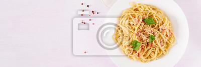 Classic homemade carbonara pasta with pancetta, egg, hard parmesan cheese and cream sauce. Italian cuisine. Spaghetti alla carbonara. Top view, banner, copy space