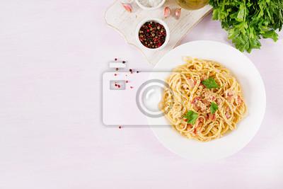 Classic homemade carbonara pasta with pancetta, egg, hard parmesan cheese and cream sauce. Italian cuisine. Spaghetti alla carbonara. Top view, flat lay, copy space