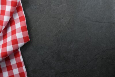 Plakat Classic italian cooking background - red checkered tablecloth on a vintage black stone kitchen countertop with copy space