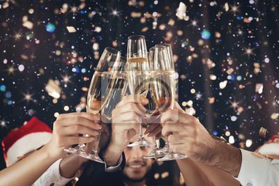 Plakat Clinking kieliszki szampana w ręce na imprezie noworocznej