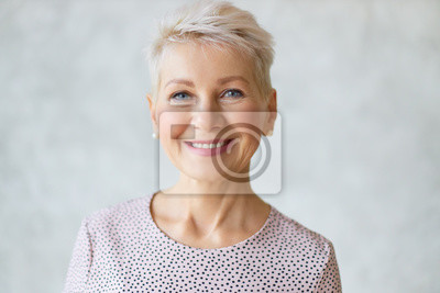 Plakat Close up image of good looking beautiful mature blonde female with blue eyes, elegant make upand pixie hairstyle smiling at camera, having confident happy facial expression, being in good mood