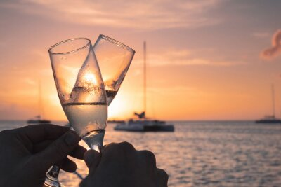 Plakat Close-up Of Hand Holding Champagne Glass Against Sunset Sky