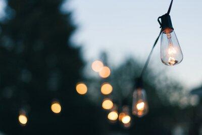 Plakat Close-up Of Illuminated Light Bulb Against Sky