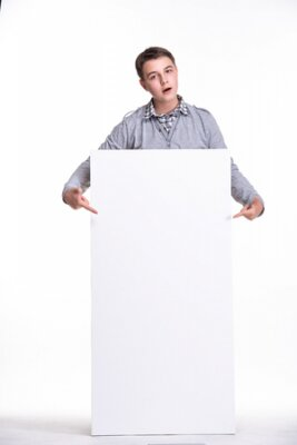 Plakat Close up of man showing white board. Guy teenager, student, schoolboy showing empty space white placard.