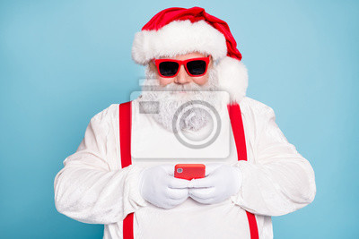 Plakat Close up photo of funny funky fat modern santa blogger in eyewear use cell phone type messages congratulations with christmas newyear wear overalls red suspenders isolated over blue color background