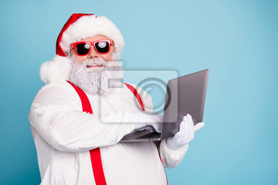 Plakat Close up photo of funny funky overweight santa claus in hipster sunglass use laptop search christmas season discounts type congratulations wear style suspenders isolated over blue color background