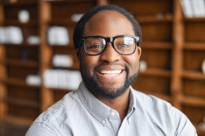 Plakat Close-up portrait of a happy African-American young man with friendly wide toothy smile, a mixed-race bearded guy wearing stylish eyeglasse and shirt looks into camera, employee profile photo