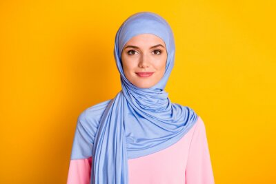 Plakat Close-up portrait of attractive cheery modest muslimah wearing blue hijab isolated over bright yellow color background