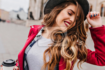 Plakat Close-up portrait of fascinating white woman with golden wavy hair posing with eyes closed on the street. Romantic relaxed girl in hat holding cup of latte.