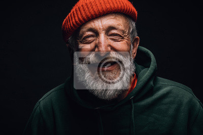 Plakat Close up portrait of happy 70-year-old optimist man with smiling wrinkled face, dressed in hipster orange hat and green hoodie, isolated over black background. Positive and cheerful at any age.