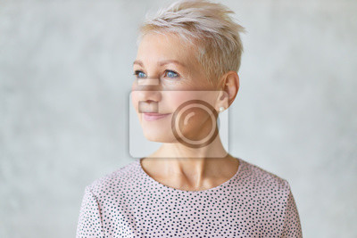 Plakat Close up studio image of beautiful attractive middle aged European lady with stylish haircut and neat make up looking away with confident smile posing isolated against marbled wall background