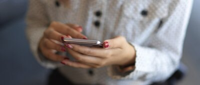 Plakat Close up view of female hands texting on smartphone