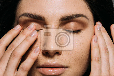 Plakat close up view of tender girl with freckles on face touching closed eyes