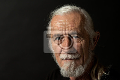 Plakat Closeup low key studio portrait of beautiful gray hair old man looking at the camera. Horizontally.