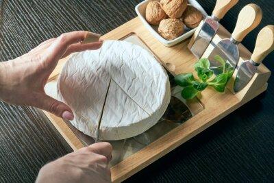 Plakat Closeup on woman cutting fresh cheese