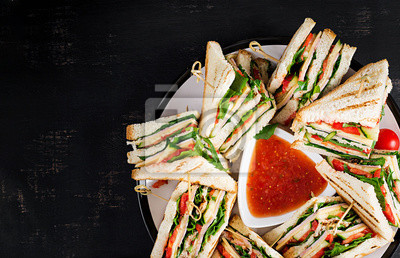 Club sandwich with ham, tomato, cucumber, cheese,  and arugula on dark background. Top view