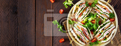 Club sandwich with ham, tomato, cucumber, cheese,  and arugula on wooden background. Banner. Top view