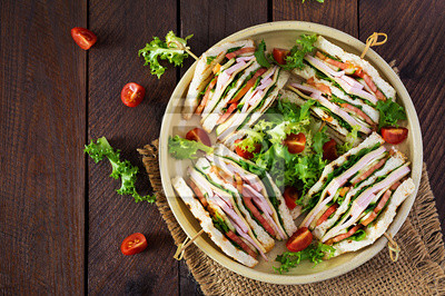 Club sandwich with ham, tomato, cucumber, cheese,  and arugula on wooden background. Top view