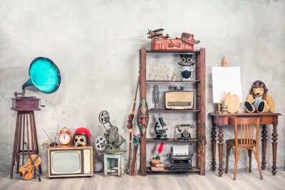 Plakat Collection of antique media devices, writers tools, gramophone, film projector, old Teddy Bear toy with canvas blank on easel, travel bag front concrete wall background. Vintage style filtered photo
