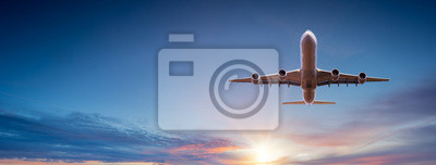 Plakat Commercial airplane flying above dramatic clouds during sunset.
