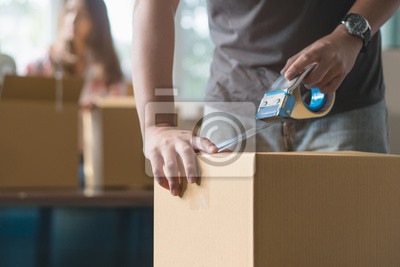 Plakat Concept young couple moving house. Close-up hand of man use tape sealing cardboard box.