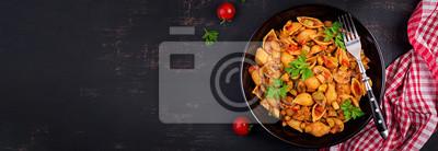 Conchiglie pasta. Italian pasta shells with mushrooms, zucchini and tomato sauce.  Top view