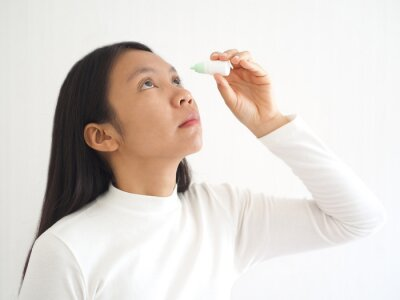 conjunctivitis in young asian woman and she using eye drop  treatment for eyeball and symptoms of pain and suffering use for health care solution or medicine product concept, close up shot photo.