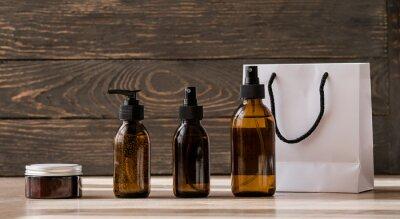 Plakat Cosmetic dark amber bottles on wooden  table