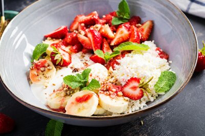 Cottage cheese or curd cheese with strawberries, bananas, walnuts in a blue bowl. Healthy food.
