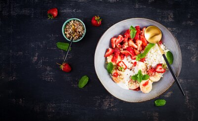 Cottage cheese or curd cheese with strawberries, bananas, walnuts in a blue bowl. Healthy food. Top view, overhead,  copy space
