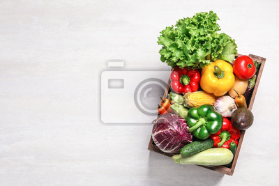 Plakat Crate with different fresh vegetables on light background, top view. Space for text