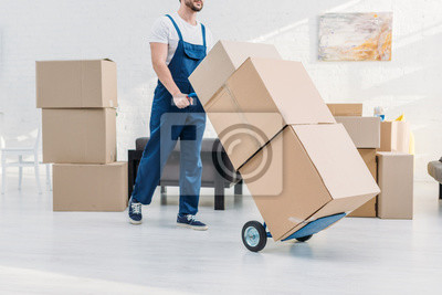 Plakat cropped view of mover in uniform transporting cardboard boxes on hand truck in apartment