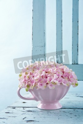 Plakat Cup full of pink hydrangea flowers on blue old shabby chic vintage chair