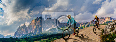 Plakat Cycling woman and man riding on bikes in Dolomites mountains andscape. Couple cycling MTB enduro trail track. Outdoor sport activity.