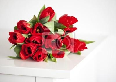 Plakat czerwone tulipany leżącego na białym stole