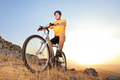 Plakat Człowiek jedzie na rowerze górskim na zachodzie słońca