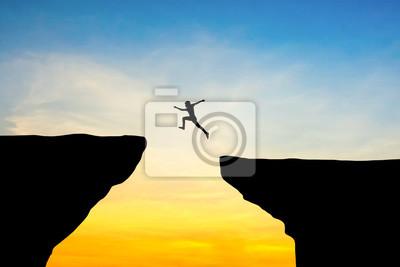 Plakat Człowiek skok przez szczelinę między hill.man skoków na klifie na tle zachodu słońca, pojęcie pomysł na biznes