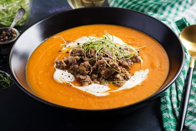 Delicious cream of pumpkin soup with roasted forcemeat made of beef minced meat in a bowl on a dark table. Thanksgiving Day.